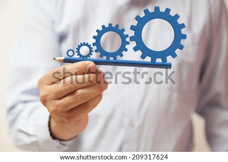 Man hand holding a pencil with gears on it
