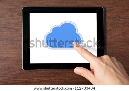 man hand holding a tablet touch computer gadget with the image of cloud - stock photo