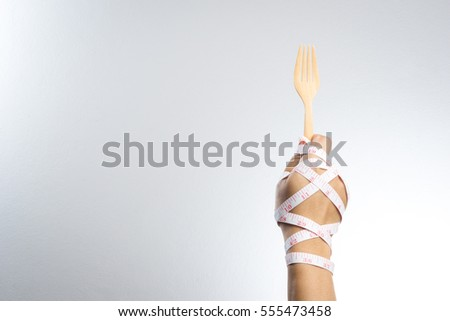 Man hand holding a wooden fork and spoon with measuring tape for diet concept