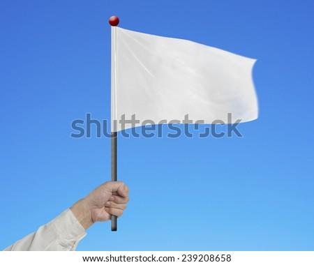 man hand holding blank white flag isolated on blue background - stock photo