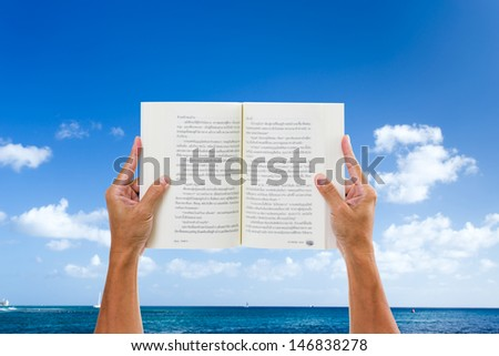 Man hand holding book with sea and blue sky background - stock photo
