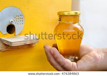 Man hand holding bottle with honey