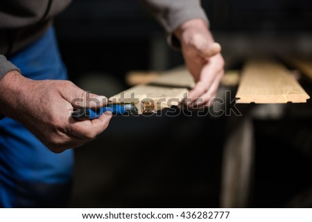 Man hand holding brush painting on wood close-up, house renovation and housing construction theme.