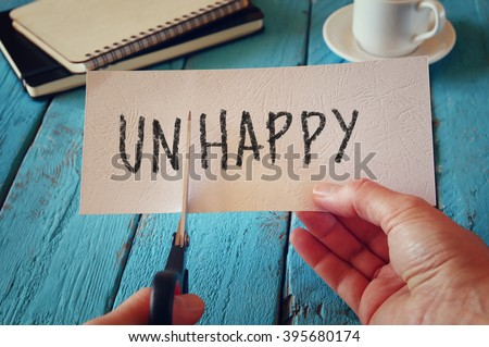 man hand holding card with the text unhappy, cutting the word un so it written happy.  retro style image  - stock photo
