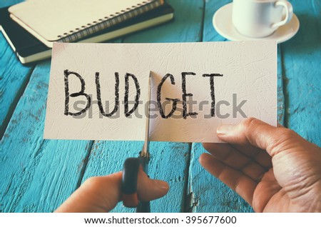 man hand holding card with the word budget. cutting budget and costs concept. retro style image - stock photo
