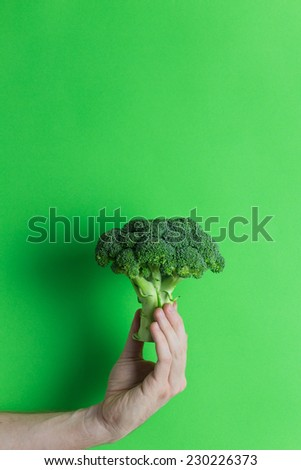 Man hand holding fresh broccoli on green background