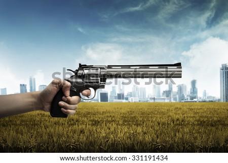 Man hand holding gun, aiming to the green grass - stock photo