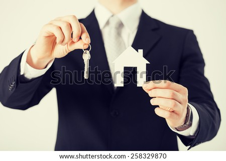 man hand holding house keys and paper house - stock photo