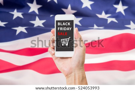 Man hand holding mbile phone with Black friday sale on screen over United State of America nation flag