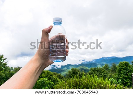 Man hand holding mineral water bottle in forest,mountains view in the morning.Water bottles on a wooden table with a background of mountain with green tree.