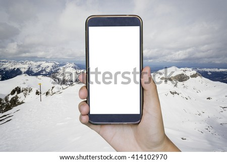 Man hand holding mobile smart phone , tablet,cellphone over Blur of snow mountain,Winter landscape in the Matterhorn - stock photo