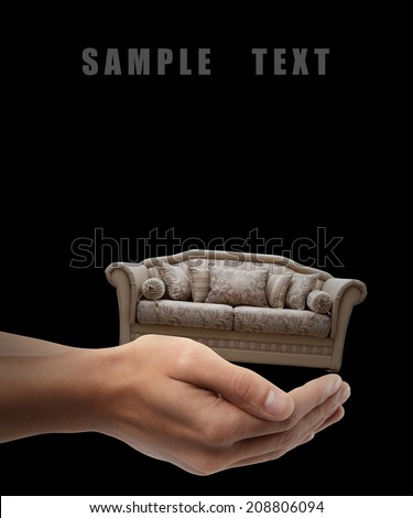 Man hand holding object ( vintage sofa ) isolated on black background. High resolution  - stock photo