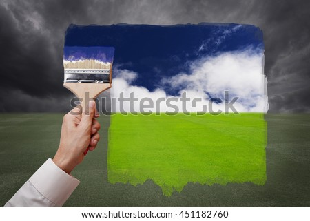 Man hand holding painting brush, paint bright day with blue sky and white cloud on green grass field replace bad cloudy day. Conceptual illustration of new better world or optimistic vision. - stock photo