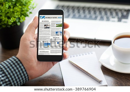 man hand holding phone with world news site on the screen in the office - stock photo