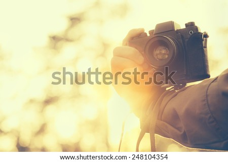 Man hand holding retro photo camera outdoor hipster Lifestyle with sunset lights on background film colors - stock photo