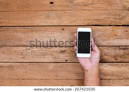 Man hand holding smart phone on wood background - stock photo