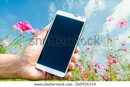 Man hand holding smartphone against spring flowers background soft focus. - stock photo