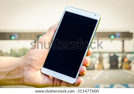 Man hand holding smartphone on blurred of cars on the road  background soft focus. - stock photo