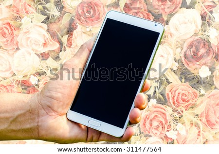 Man hand holding smartphone on rose vintage background soft focus. - stock photo