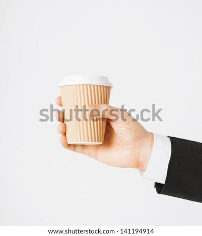 man hand holding take away coffee cup - stock photo