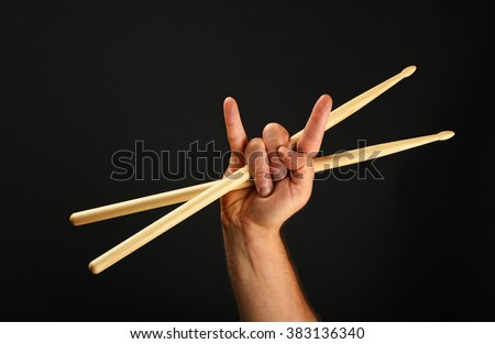 Man hand holding two crossed wooden drumsticks with devil horns rock metal gesture sign over black background, front view - stock photo