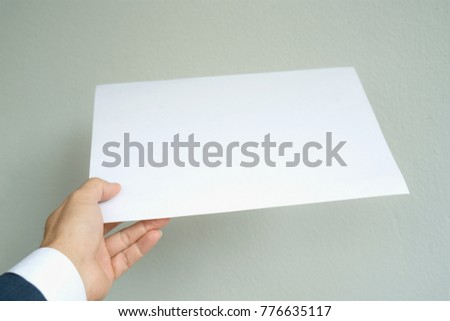 Man hand holding white paper A4 size on gray background,mock up style,business concept.