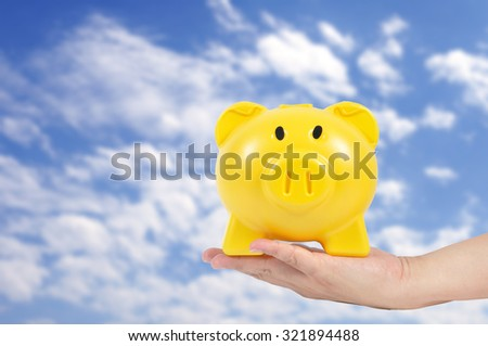 Man hand holding yellow piggy bank with blue sky - stock photo