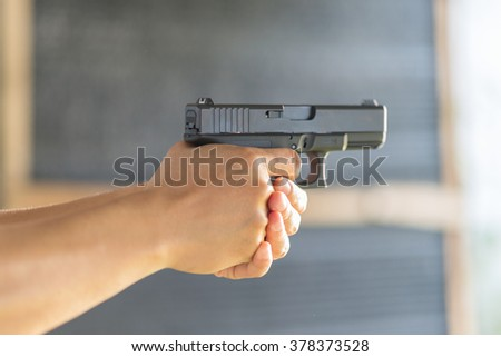 Man hand holds gun shoot the target ( in selective focus ) - stock photo