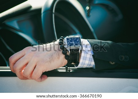man hand in elegant suit with watch and bracelet lean on car window, closeup natural light, shallow depth of field - stock photo