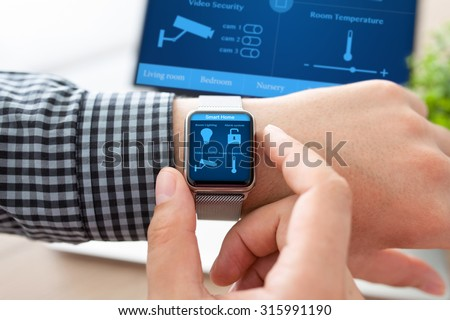 man hand in watch with program smart home on the screen against the background of computer  - stock photo