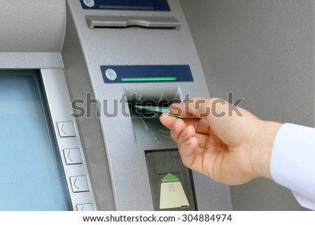 man hand inserting credit card to ATM - stock photo