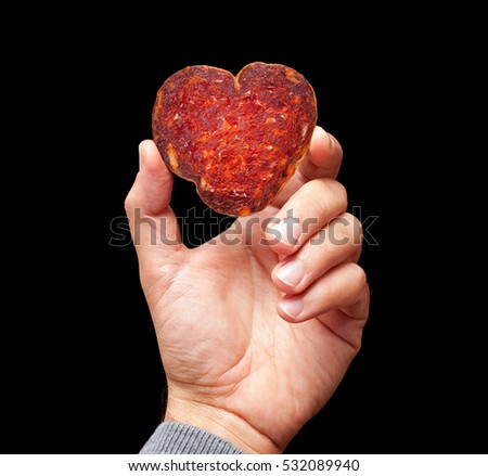 Man hand is holding a heart shape slice of croatian kulen on a black background.