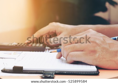 Man hand is holding pencil thinking about savings finance and calculator at home.
