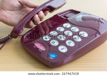 man hand is holding the old telephone - stock photo