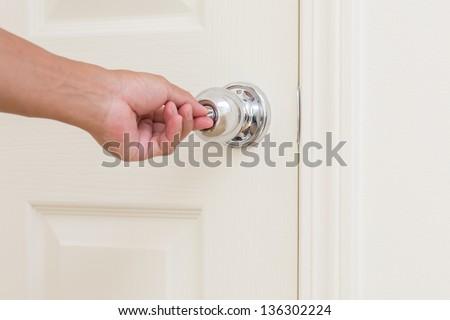 Man hand lock door knob - stock photo