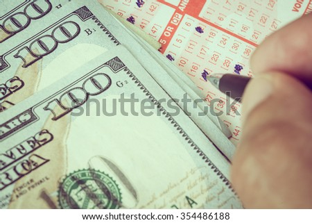 Man hand marking down to select number in lotto ticker with dollar bill - stock photo