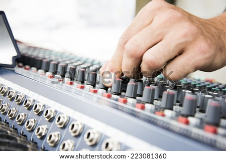 Man hand on a console with buttons as music equipment for concerts