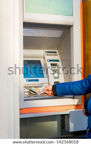 Man hand on atm taking money