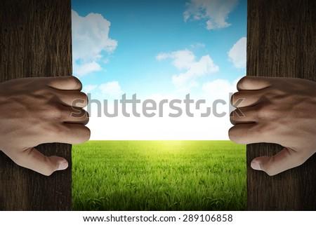 Man hand open door into green grass meadow - stock photo