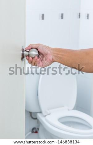 Man hand open toilet door - stock photo