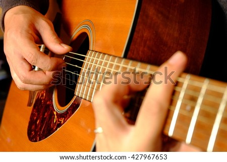 Man'hand playing acoustic guitar,close up