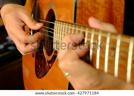 Man'hand playing acoustic guitar, close up