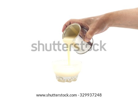 Man hand pouring condensed milk into a bowl isolated - stock photo