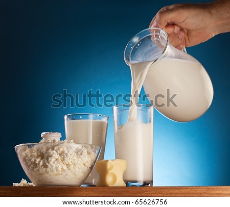 Man hand pouring milk from jar into the glass. Isolated on a  blue. - stock photo