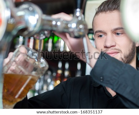 Man hand pouring of beer behind the bar
