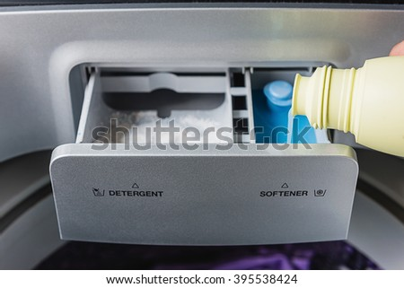 man hand pouring softener into the washing machine - stock photo