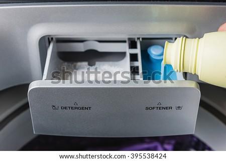 man hand pouring softener into the washing machine - stock photo
