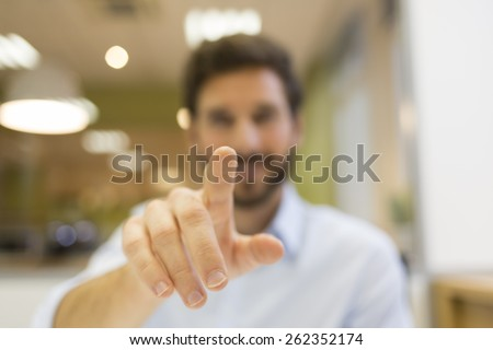 Man hand pushing a digital screen on office background - stock photo