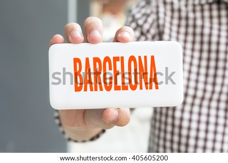 Man hand showing BARCELONA word phone with  blur business man wearing plaid shirt. - stock photo