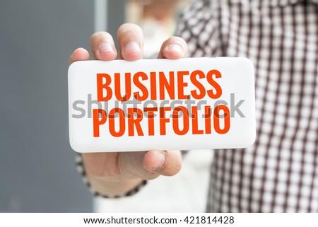 Man hand showing BUSINESS PORTFOLIO word phone with  blur business man wearing plaid shirt. - stock photo